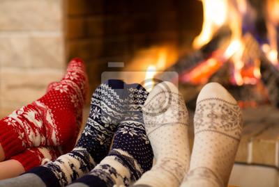 Fototapeta Stopy w skarpetkach wełnianych pobliżu kominka w czasie zimy
