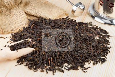 stos herbata czarna, drewniana łopatka, czajniczek na stole
