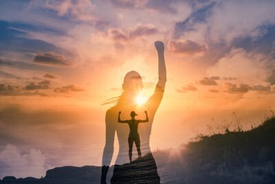 Fototapeta Strong confident woman on mountain top flexing arms facing the sunset. People feeling inspire, and finding inner strength concept. double exposure.