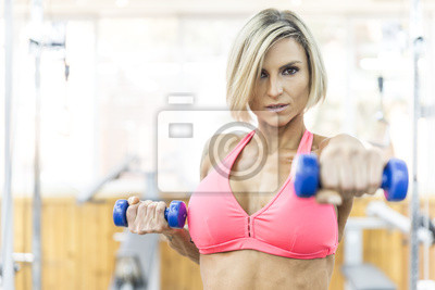 Strong woman weightlifting at the gym looking