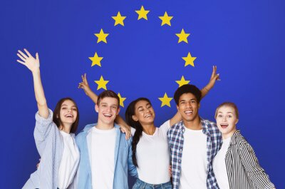 Fototapeta Student Exchange Programs In Eu. Multiracial Teens Posing Over Europe Union Flag