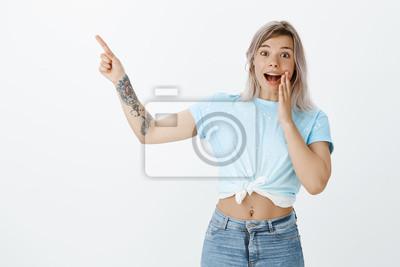 Studio strzał zdziwiony, przystojny kobieta z tatuażami i kolczyk w brzuchu, stojąc w szoku i pod wrażeniem, uśmiechając się szeroko z podniecenia, wskazując w lewym górnym rogu z podniesionym palcem