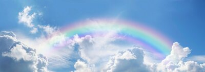 Fototapeta Stunning blue sky panoramic rainbow - big fluffy clouds with a giant arcing rainbow against a  beautiful summer time blue sky with copy space for messages