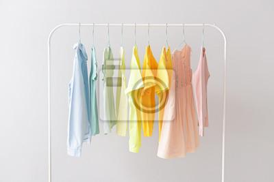 Fototapeta Stylish kid clothes hanging on rack against light background
