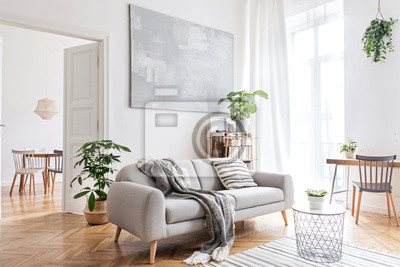 Fototapeta Stylish scandinavian living room with design furniture, plants, bamboo bookstand and wooden desk. Brown wooden parquet. Abstract painting on the white wall. Nice apartment. Modern decor of bright room