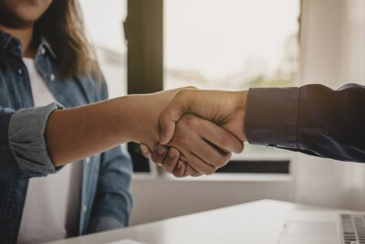 Fototapeta Successful young asian woman, man  partnership, team handshake together at office after project done, good deal. .Happy business people, worker meeting, shaking hands concept..