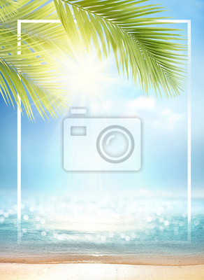 Fototapeta Summer background with frame, nature of tropical golden beach with rays of sun light and leaf palm. Golden sand beach close-up, sea water,  blue sky, white clouds. Copy space, summer vacation concept.
