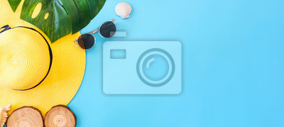 Fototapeta summer blue banner with yellow hat ,sunglasses,seashell and monstera leaf on blue background top view.