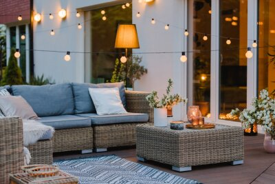 Fototapeta Summer evening on the terrace of beautiful suburban house with patio with wicker furniture and lights