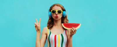 Fototapeta Summer fashion portrait of young woman in headphones listening to music with juicy slice of watermelon, female model blowing her lips posing on a colorful blue background