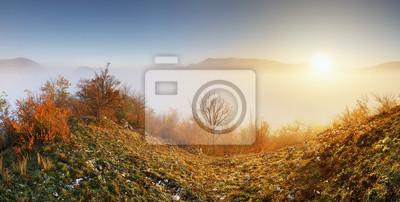 Fototapeta Sun over clouds mist in mountain landcape at sunrise