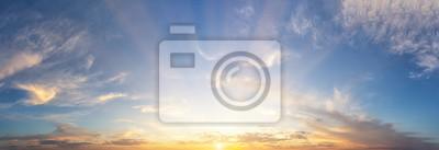Fototapeta Sunset cloudy sky with the orange sun