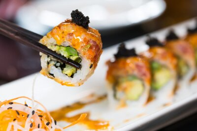 Fototapeta Sushi roll z czarnymi pałeczkami