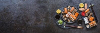 Fototapeta sushi rolls with rice and fish, soy sauce on a dark stone background