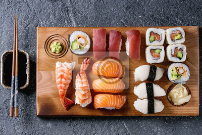 Fototapeta Sushi Zestaw nigiri i sushi rolkach na drewnianych obsługujących płytę z sosu sojowego i pałeczki na czarnym tle tekstury kamień. Widok z góry z przestrzeni kosmicznej. Menu w Japonii