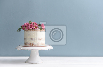 Fototapeta Sweet cake with floral decor on table against color background