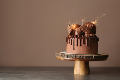 Fototapeta Sweet chocolate cake with sparklers on table against color background