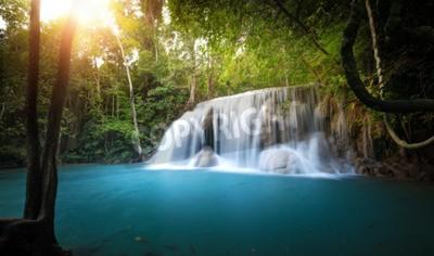 Fototapeta Światło słoneczne świecił poprzez drzew i liści z lasów tropikalnych i wodospad przepływa do niebieskiej wody stawu