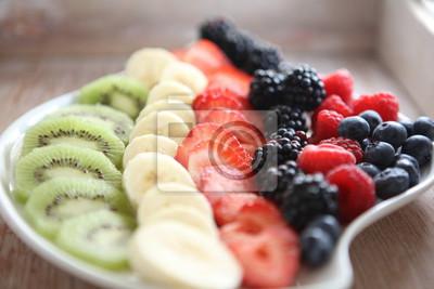 Świeże kolorowe owoce i jagody w drewnianej misce na stole rustykalnym
