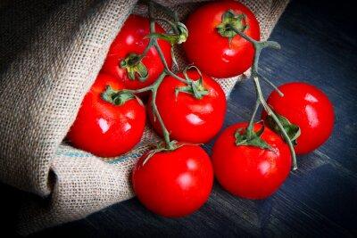 Fototapeta Świeże pomidory na jutowym worku na drewnie