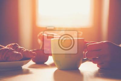 świeże śniadanie z gorącą kawę i rogalika w godzinach porannych sunligh
