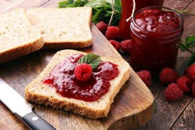 Świeży dżem malinowy z grzanką lub chlebem na śniadanie.