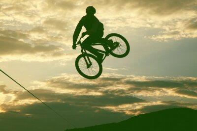 Fototapeta Sylwetka człowieka robi skok o rower BMX przed zachodem słońca