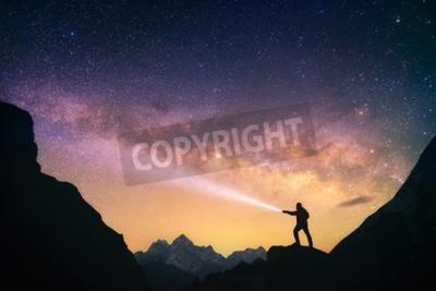 Fototapeta Sylwetka człowieka stojącego przed Czarną Drogą w górach z latarką w dłoniach. Nepal, region Everest, widok na mount Thamserku 6.608 m od wioski Thame 3,750 m.