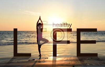 Fototapeta Sylwetka dziewczyny uprawiania jogi drzewa vrikshasana ułożenia na tropikalnej plaży z nieba tle zachodu słońca, obserwując zachód słońca, stojąc w ramach koncepcji sformułowanie zdrowego życia.