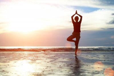Fototapeta Sylwetka kobieta uprawiania jogi na plaży.