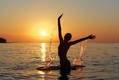 Fototapeta Sylwetka Kobiety w wodzie na TLE słońca zachodzącego