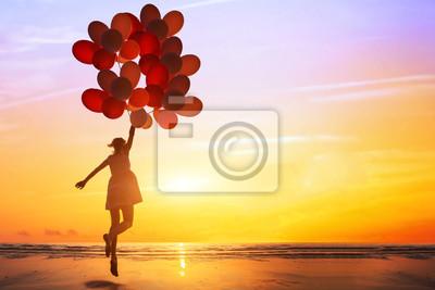 Fototapeta szczęście lub wymarzony pojęcie, sylwetka szczęśliwa kobieta skoki z wielobarwny balony o zachodzie słońca na plaży