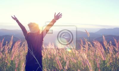 Fototapeta Szczęśliwa kobieta Cieszy się naturę na trawy łące na górze halnej falezy z zmierzchem plenerowym. Pojęcie wolności.