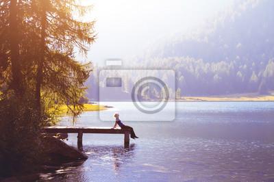Fototapeta Szczęśliwa kobieta siedzi na molo i uśmiecha, koncepcja szczęścia lub inspiracji, cieszyć się życiem