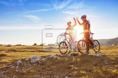 Fototapeta szczęśliwa para idzie na górskiej asfaltu drogowego w lesie na rowery z hełmami dając sobie wzajemnie wysoki piąty