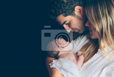 Fototapeta Szczęśliwa para obejmując i patrząc noworodka na ciemnym tle