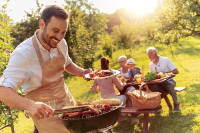 Fototapeta Szczęśliwa rodzina o przyjęcie przy grillu na podwórku