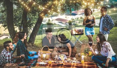 Fototapeta Szczęśliwi przyjaciele bawią się w winnicy po zachodzie słońca - Młodzieżowy tysiącletni camping na pikniku na świeżym powietrzu pod żarówkami - Koncepcja przyjaźni młodzieży z młodymi ludźmi pijącymi