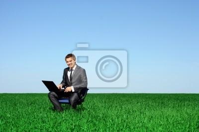 Szczęśliwy człowiek na polu z laptopem