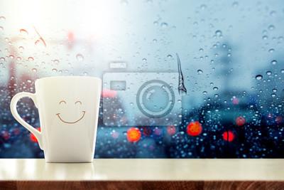Fototapeta Szczęśliwy Kubek kawy ze smilely twarzą na biurku wewnątrz szkła okno, niewyraźne korków w mieście jak na zewnątrz, relaks w kawiarni w deszczowy dzień