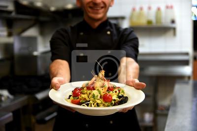 Fototapeta Szczęśliwy kucharz trzyma pyszne makarony