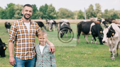 Fototapeta szczęśliwy ojciec i syn uśmiecha się do kamery, stojąc w pobliżu wypasu bydła na farmie