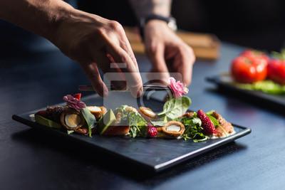 Fototapeta Szef kuchni kropi pikantność na naczyniu w handlowej kuchni