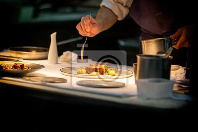 Fototapeta Szef kuchni przygotowuje danie z mięsem na talerzu pod światłem. Szef kuchni jest drobiazgowy.