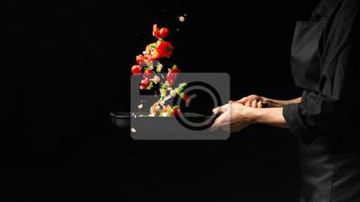 Fototapeta Szef kuchni przygotowuje warzywa na ciemnym tle na patelni grillowej