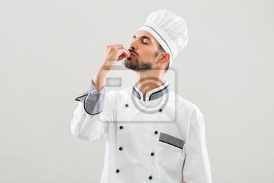 Fototapeta Szef kuchni wykazuje smaczne znak na szarym tle.