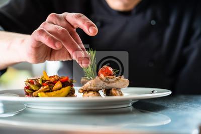 Fototapeta Szef kuchni wykończa i przyrządza potrawy, które przygotował, danie z mięsem wieprzowym i warzywami