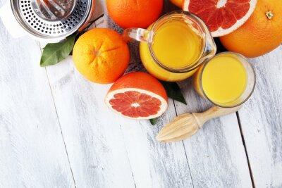 Szkło grapefruitowy sok i plasterki pomarańczowa owoc na drewnianym tle.