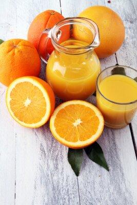 Szkło sok pomarańczowy i plasterki pomarańczowa owoc na drewnianym tle.