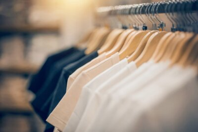 Fototapeta T-shirts on hangers. Shopping in store. Clothes on hangers in shop for sale